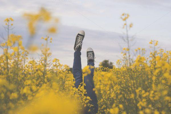 vrouw die op campervakantie is ligt in een veld vol bloemen