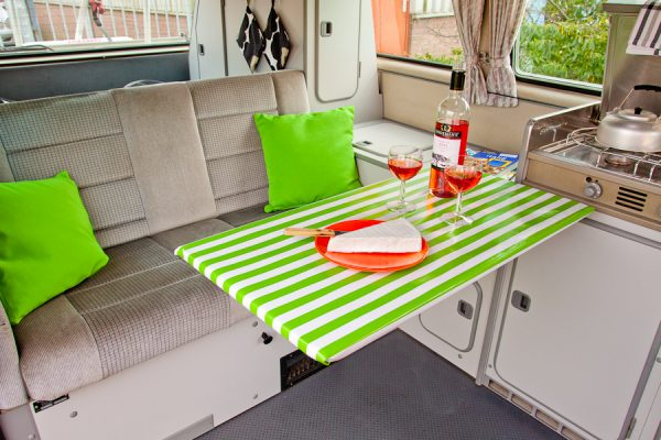 uitgedraaide tafel met glas wijn in een vw t3 hoogdak camper
