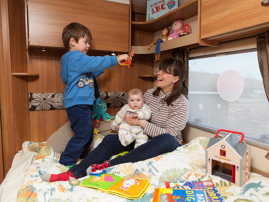 gezin op bed in Fiat alkoof camper